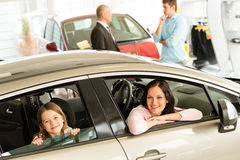Mother and daughter trying car in dealership Stock Photos