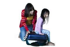 Mother and daughter trying to close a suitcase Stock Image