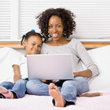 Mother and daughter typing on laptop. On bed in bedroom royalty free stock image
