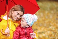 Mother and daughter with umbrella in autumn park. On rainy day stock image