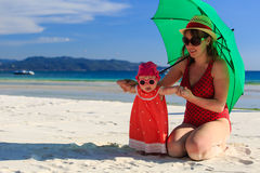 Mother and daughter with umbrella on beach vacation Stock Image