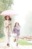 Mother and daughter with umbrella walking in park. Royalty Free Stock Photos