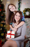 Mother and daughter under Christmas tree Stock Photos