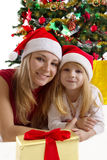 Mother and daughter under Christmas tree Royalty Free Stock Photo