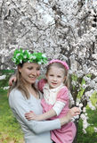 Mother and daughter under spring tree Stock Images