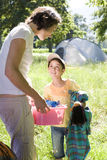 Mother and daughter (8-10) unloading car on camping trip, woman carrying pink container, smiling. Mother and daughter (8-10) unloading car on camping trip, women Royalty Free Stock Photos