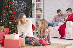 Mother and daughter unwrapping gifts. Father and son on sofa Royalty Free Stock Photography
