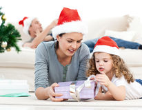 Mother and daughter unwrapping a present Stock Photos