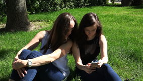 Mother and daughter use information technology of mobile phone in the park.  stock video footage