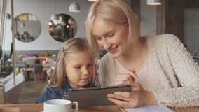 Mother and daughter use tablet at the cafe. Cute young woman and her daughter using tablet at the cafe. Pretty blond woman telling something to her child stock footage