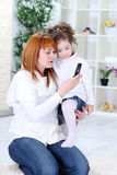 Mother  and daughter using cell phone Stock Images
