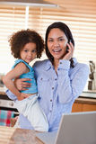 Mother and daughter using cellphone in the kitchen together Stock Photography