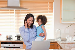 Mother and daughter using cellphone and laptop in the kitchen Stock Images
