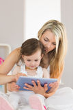 Mother and daughter using digital tablet on bed at home Stock Photo