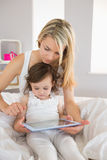 Mother and daughter using digital tablet on bed. Mother and young daughter using digital tablet on bed at home Royalty Free Stock Photo