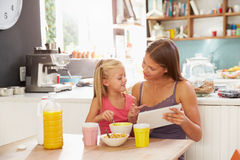 Mother And Daughter Using Digital Tablet At Breakfast Table Stock Photos