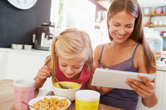 Mother And Daughter Using Digital Tablet At Breakfast Table Stock Image