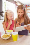 Mother And Daughter Using Digital Tablet At Breakfast Table Stock Images