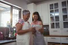 Mother and daughter using digital tablet in kitchen Stock Image