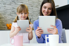 Mother and daughter using a digital tablet in kitchen Royalty Free Stock Photos