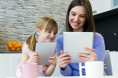 Mother and daughter using a digital tablet in kitchen Stock Photo