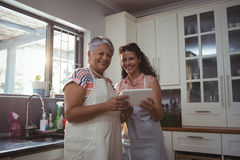 Mother and daughter using digital tablet in kitchen Stock Photo