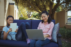 Mother and daughter using digital tablet and laptop while relaxing on couch Stock Photo