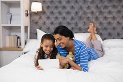 Mother and daughter using digital tablet while lying on bed at home Stock Images