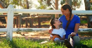 Mother and daughter using digital tablet and mobile phone in ranch 4k. Mother and daughter using digital tablet and mobile phone in ranch on a sunny day 4k stock video