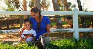 Mother and daughter using digital tablet and mobile phone in ranch 4k. Mother and daughter using digital tablet and mobile phone in ranch on a sunny day 4k stock video footage