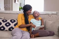 Mother and daughter using digital tablet while sitting on sofa at home Royalty Free Stock Photos