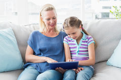 Mother with daughter using digital tablet on sofa Stock Photos