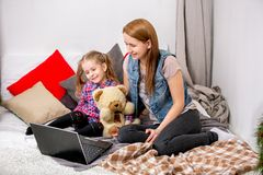Mother and daughter using laptop on bed in bedroom. They look at the display and laugh. royalty free stock photo
