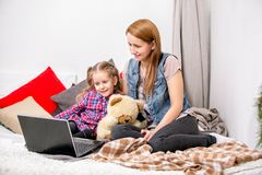 Mother and daughter using laptop on bed in bedroom. They look at the display and smile. stock image