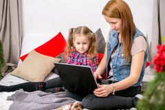 Mother and daughter using laptop on bed in bedroom. Mom shows daughter information on laptop display royalty free stock photo