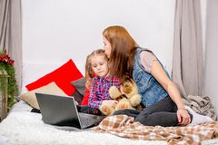 Mother and daughter using laptop on bed in bedroom. Mother hugging and kissing daughter royalty free stock images