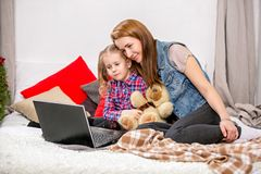 Mother and daughter using laptop on bed in bedroom. Mother with love and care embraces and kisses daughter stock image