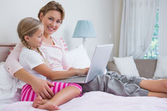 Mother and daughter using laptop in bed Stock Images