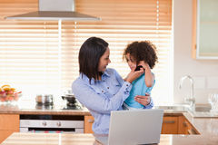 Mother and daughter using laptop and cellphone in the kitchen to Royalty Free Stock Photography