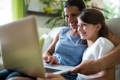 Mother and daughter using laptop and digital tablet in the living room Stock Photo