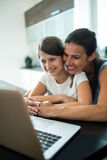 Mother and daughter using laptop and digital tablet in the living room Stock Image