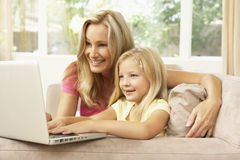 Mother And Daughter Using Laptop At Home Royalty Free Stock Photos