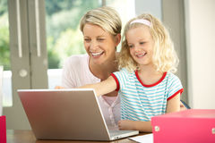 Mother And Daughter Using Laptop At Home. Smiling Royalty Free Stock Images