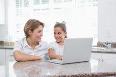 Mother and daughter using laptop Stock Photos