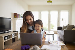 Mother And Daughter Using Laptop At Home Together Stock Photography