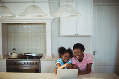Mother and daughter using laptop in kitchen Stock Photo
