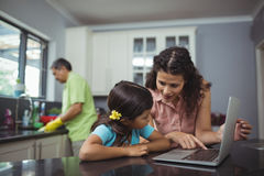 Mother and daughter using laptop in kitchen Royalty Free Stock Images