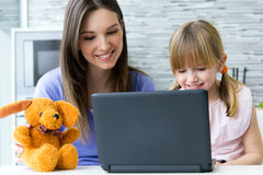 Mother and daughter using laptop in the kitchen Stock Photo
