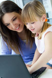 Mother and daughter using laptop in the kitchen Royalty Free Stock Image