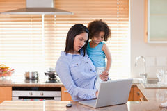 Mother and daughter using laptop in the kitchen together Royalty Free Stock Image